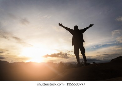Silhouette of hiker standing on top of hill and enjoying sunrise over the valley.  The man thank God on the mountain.