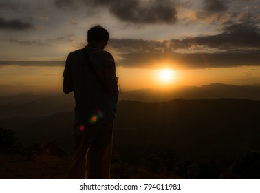 silhouette hiker waiting sunset at the top of mountain