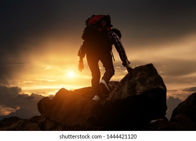Silhouette of Hikers climbing up mountain cliff in sunset. Concept of limits of life and Hiking success full.