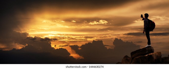 Silhouette of Hikers climbing up mountain cliff in sunset selfie with smartphone. Concept of limits of life and Hiking success full, Sports banner with copy space