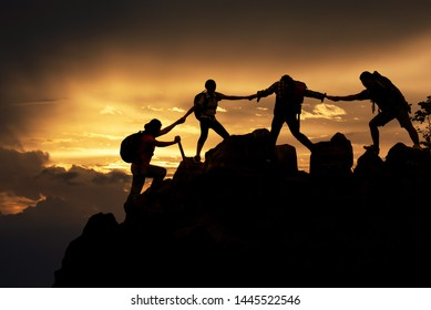 Silhouette of Hikers climbing up mountain cliff. Climbing group helping each other while climbing up in sunset. Concept of help and teamwork, Limits of life and Hiking success full.