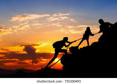 Silhouette of hikers climbing up on the mountain,team work and helping concept.