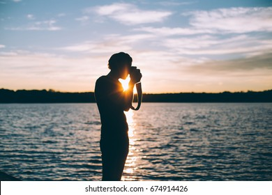 Silhouette of hipster professional photographer making photographs of nature lake national park skies and forests