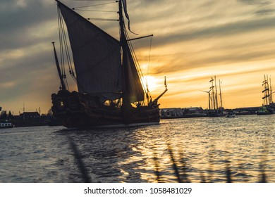 silhouette of historic sailboats on the rivers of the Netherlands. The evening falls in and in an atmospheric summer evening the boats sail over the water surface with sails and masts