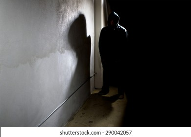 Silhouette of a hooded criminal stalking in the shadows of a dark street alley.  The man is a criminal waiting to ambush victims. The wall provides copyspace.