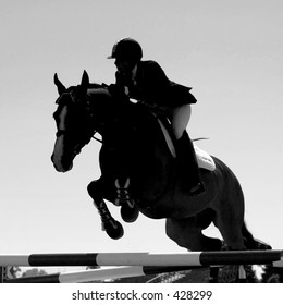 Silhouette of horse and rider jumping in black and white