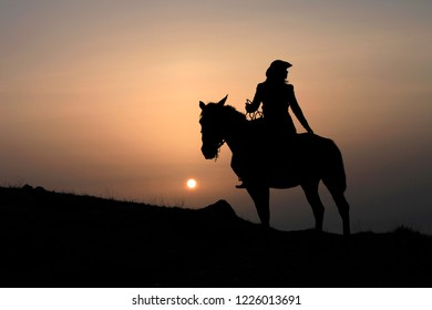 Silhouette of a horsewoman on a horse at sunset
