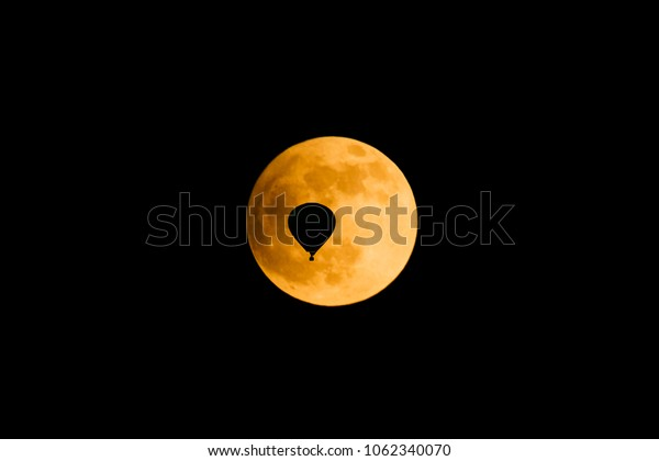 Silhouette of a hot air balloon in front of the full moon