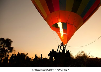 Silhouette hot air balloon landing with many people
