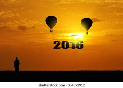 silhouette of hot air balloon with year 2016 raised at twillight.
