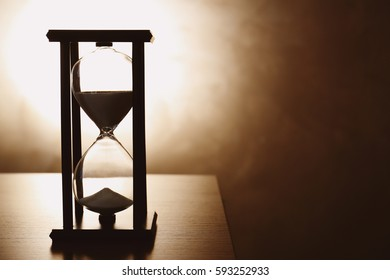 Silhouette of hourglass with sand on dark background