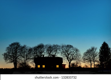 silhouette of house with bare trees on dark blue sky in evening