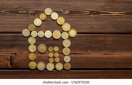 Silhouette of a house made of coins on a wooden background. The concept of mortgages, savings for the purchase of housing, utility bills, building leases and real estate investments.