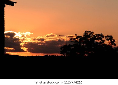 Silhouette of a house and some trees with the sunset in the background