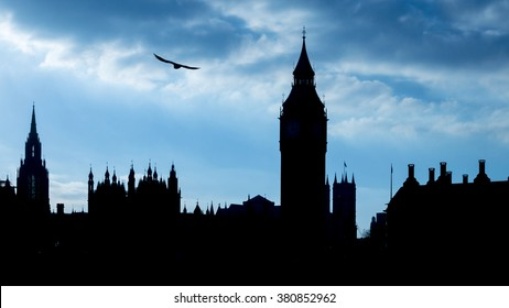 Silhouette of the Houses of Parliament against a blue overcast sky, London, Britain.