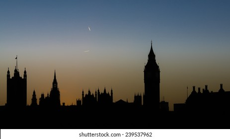Silhouette of the Houses of Parliament and Big Ben at sunset with contrails of overflying planes in the sky