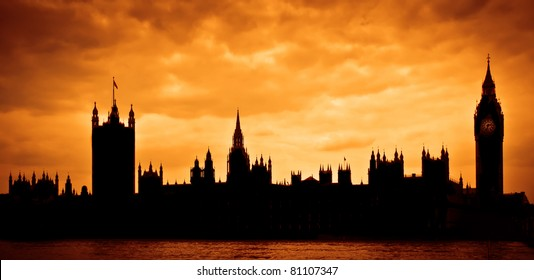 Silhouette of the Houses of Parliament and Big Ben across River Thames in London, UK with dramatic sky during sunset