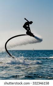 Silhouette of a hover board rider at sea