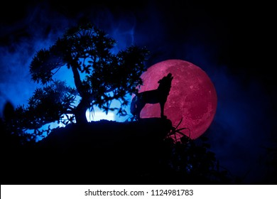 Silhouette of howling wolf against dark toned foggy background and full moon or Wolf in silhouette howling to the full moon. Halloween horror concept. Selective focus