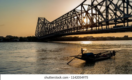 Silhouette of Howrah Bridge at the time of Sunrise.  Howrah Bridge is a bridge with a suspended span over the Hooghly River in West Bengal.