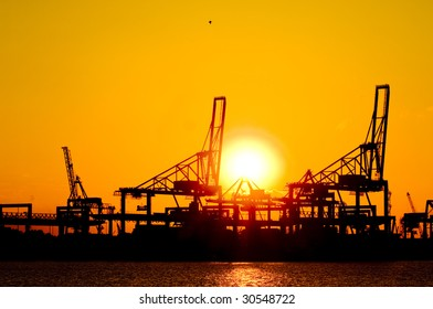 Silhouette of huge commercial harbor against a setting sun on a summer afternoon