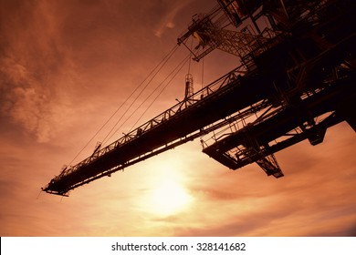 Silhouette of huge mining drill machine photographed from a ground with a wide angle lens into the sun. Dramatic and colorful red sky in background.