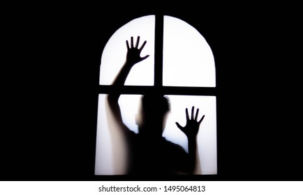 The silhouette of a human in front of a door at night.Scary scene Halloween concept of blurred silhouette