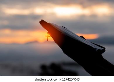 Silhouette der menschlichen Hand hält Bibel und Kreuz, der Hintergrund ist der Sonnenaufgang., Konzept für christliche, christliche, katholische Religion, göttliche, himmlische, Himmelskörper oder Gott.