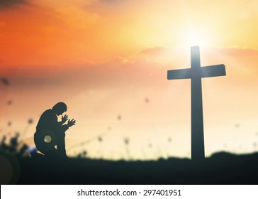 Silhouette human kneeling and praying over the cross on supernatural sunset background.