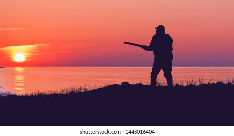 Silhouette of a hunter against the evening purple sunset sky. Stands at the ready with a gun.