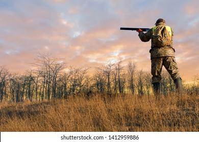 Silhouette of a hunter on the background of the morning red dawn. Stands at the ready with a gun, aims at flying game.