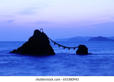 The silhouette of the husband-and-wife rock (Meotoiwa), in Ise, Mie, Japan. A torii (Red gate to a Japanese Shrine) and a Shimenawa (enclosing rope made by rice straw) on the rock.