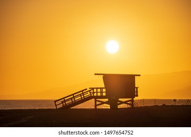 Silhouette of the iconic lifeguard tower with the setting sun in the background at the Santa Monica State Beach in California.