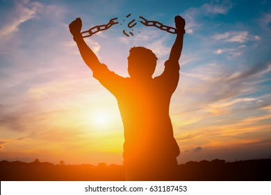 Silhouette image of a businessman with broken chains in sunset.