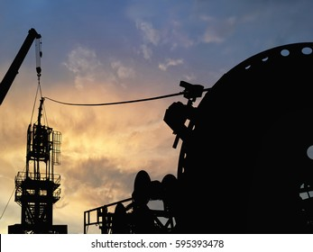 Silhouette image of coiled tubing workover rig unit with dramatic sky during sunset during well servicing the oil and gas industry