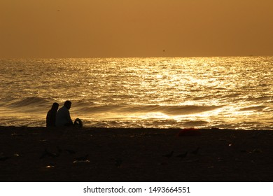 silhouette image of couples. they sitting and talking/discussing in the beach at morning and enjoying the nature of sea