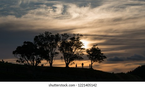 Silhouette image of people walking at the top of Mt Eden at Sunset, Auckland, New Zealand