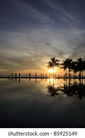 Silhouette Image of sunset at swimming pool on the beach of Thailand