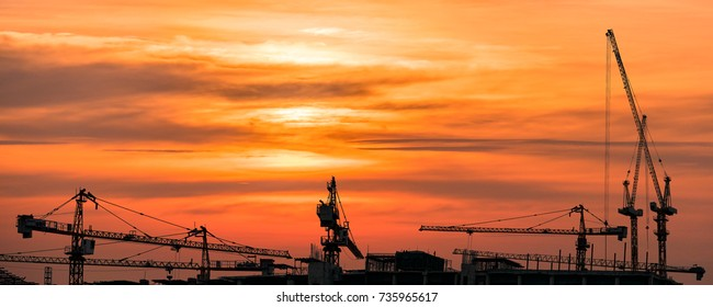 The silhouette image of tower cranes at the real estate and building construction site with the background of golden sky of sun set.