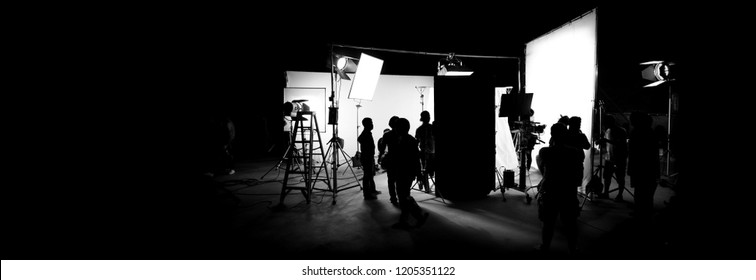 Silhouette images of video production behind the scenes or b-roll or making of TV commercial movie that film crew team lightman and cameraman working together with director in big studio  - Shutterstock ID 1205351122