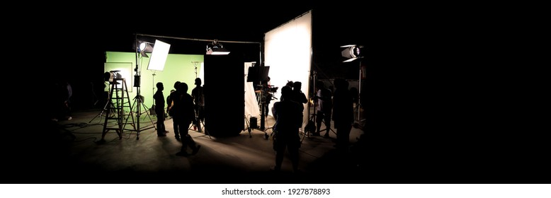 Silhouette images of video production behind the scenes. making of TV commercial movie that film crew team lightman and cameraman working together with film director in studio. film production concept