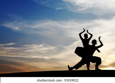 Silhouette of Indian cultural duet dancers posing on a hill against a surreal dramatic sunset sky.