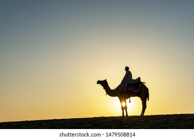 Silhouette of Indian man and camel during sunrise at Thar desert in Jaisalmer, Rajasthan, India.
