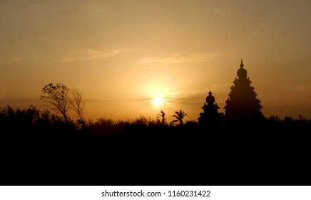 Silhouette of Indian temples and trees on sunset background. Orange sky