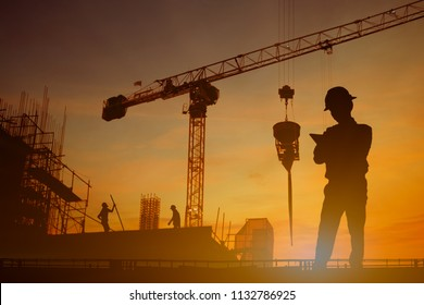 Silhouette of inspector working at construcktion on twilight background.
