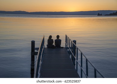 Silhouette of International Two women sit  on the bridge  beautiful background.at the beach at sunset. concept for relationship and relax lifestyle,