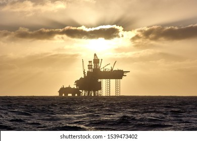Silhouette of a jack up drilling rig in the North Sea at sunset. North sea offshore platform for oil and gas.