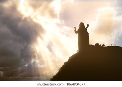 Silhouette of Jesus Christ praying to god with a dramatic sky background