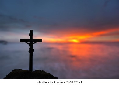 Silhouette Jesus and the cross over blurred sunset