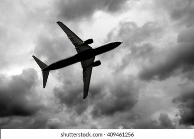 Silhouette of jet in dark cloudy sky